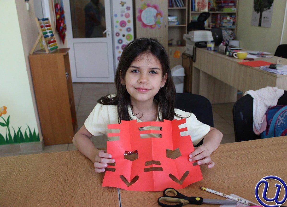 Снимка на дете от детската занималня на Интелекти, което е завършило своята задача по изрязване.