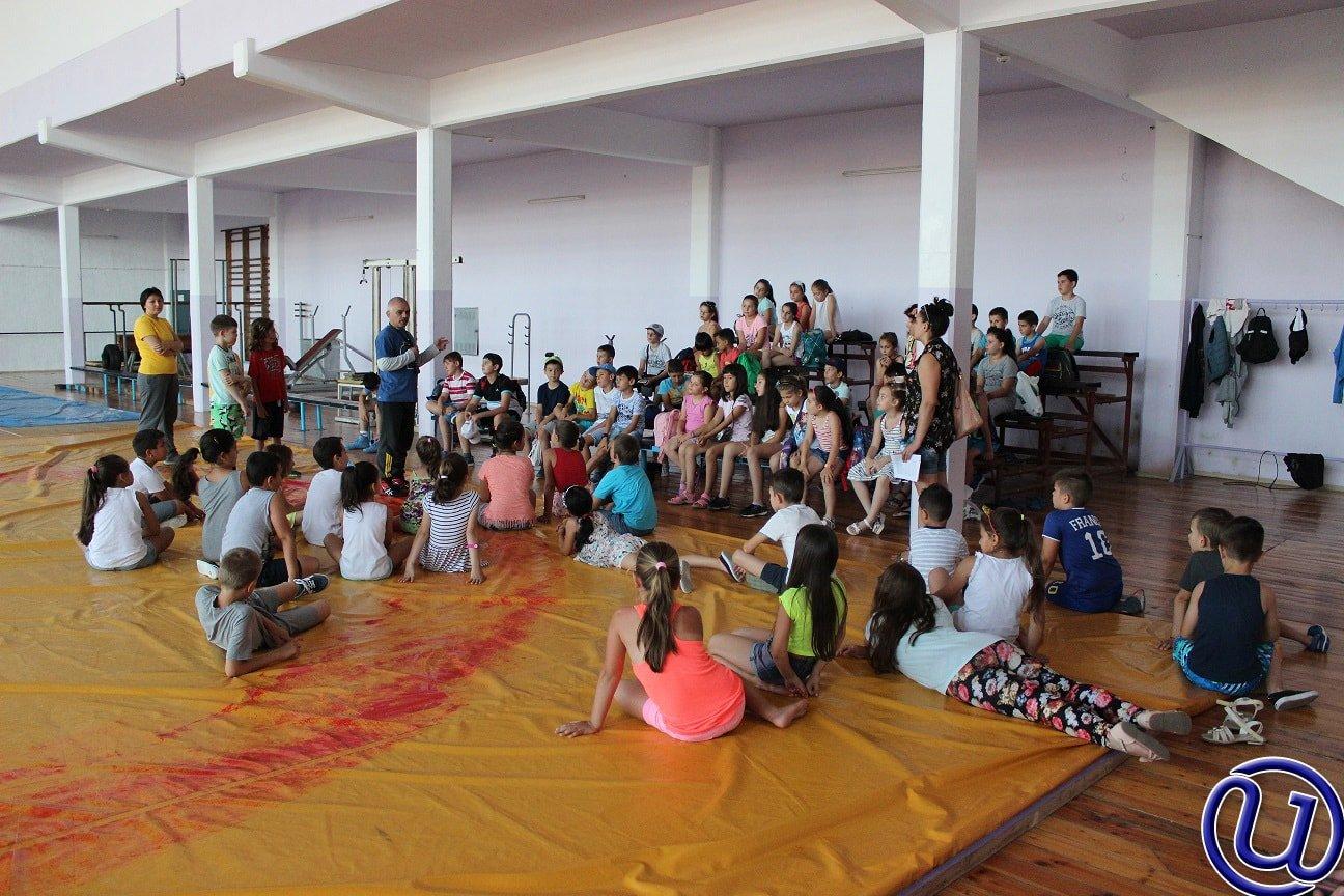 Снимка на децата от детската занималня на Интелекти, които слушат как учителя по гимнастика говори.
