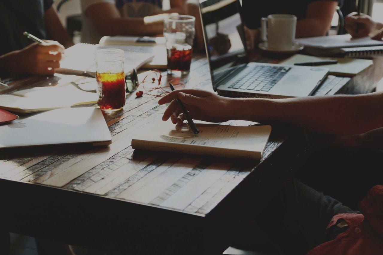 Среща на екип от хора, които говорят помежду си и правят записки.