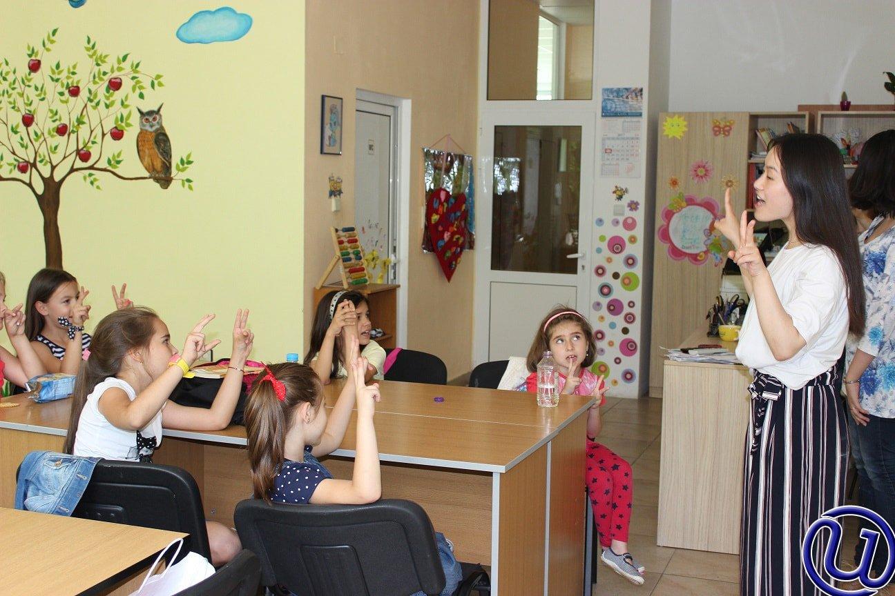 Снимка на децата от детската занималня на Интелекти, които се учат да броят и пишат, заедно с учителките.
